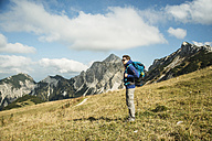 Austria, Tyrol, Tannheimer Tal, hiker with backpack on alpine meadow - UUF002235