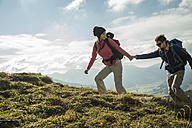 Austria, Tyrol, Tannheimer Tal, young couple hiking hand in hand on alpine meadow - UUF002256