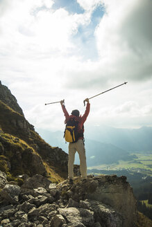 Austria, Tyrol, Tannheimer Tal, young woman with hiking poles cheering on mountain top - UUF002282