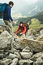 Austria, Tyrol, Tannheimer Tal, young couple hiking on rocks - UUF002288