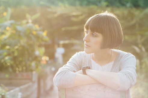 Portrait of pensive woman with bob hairdo sitting in a garden - FX000071