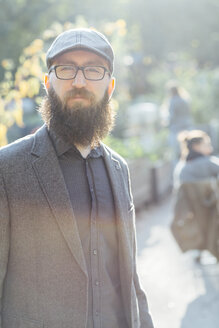Portrait of beared man wearing glasses and a cap in a garden - FX000073