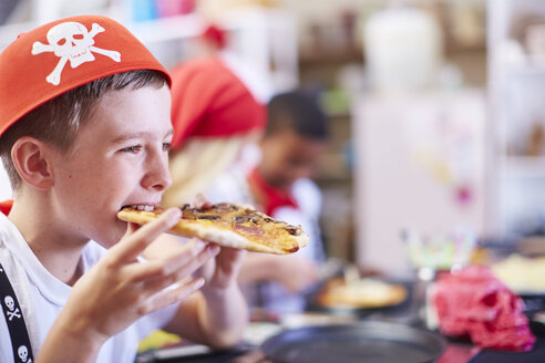 Boy dressed up as pirate eating pizza on a party - ZEF001344