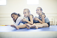 Three girls doing gymnastics exercise on floor - ZEF001313