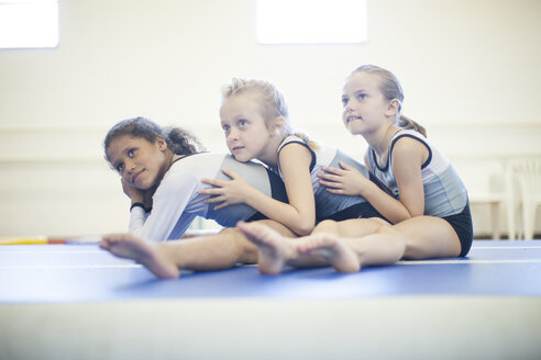 Three girls doing gymnastics exercise on floor - ZEF001313