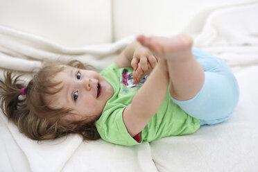 Relaxed baby girl lying on white blanket - SHKF000016