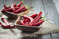 Wooden bowl of red chili peppers on jute and wood - SBDF001331