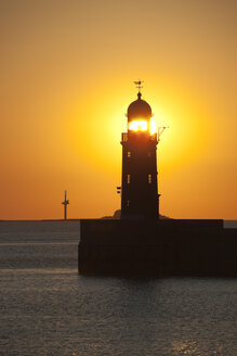 Germany, Bremen, Bremerhaven, Lighthouse on the pier at sunset - OLEF000042