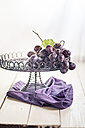 Wire fruit bowl of blue grapes on purple cloth and wood - SBDF001351