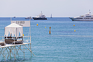 France, Provence, Cote d'Azur,view to  jetty of luxury restaurant and moored motor yachts in the background - WD002721