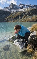 Austria, Salzburg State, Pinzgau, woman at drinking water from Weisssee mountain lake - MKFF000133
