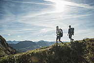 Austria, Tyrol, Tannheimer Tal, young couple hiking on mountain trail - UUF002197