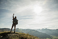 Austria, Tyrol, Tannheimer Tal, young man cheering on mountain top - UUF002180