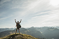 Austria, Tyrol, Tannheimer Tal, young man cheering on mountain top - UUF002179