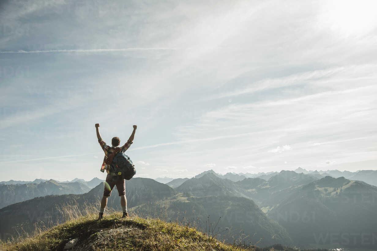 Austria, Tyrol, Tannheimer Tal, young man cheering on mountain top - UUF002179 - Uwe Umstätter/Westend61