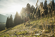 Austria, Tyrol, Tannheimer Tal, young couple hiking in sunlight on alpine meadow - UUF002148