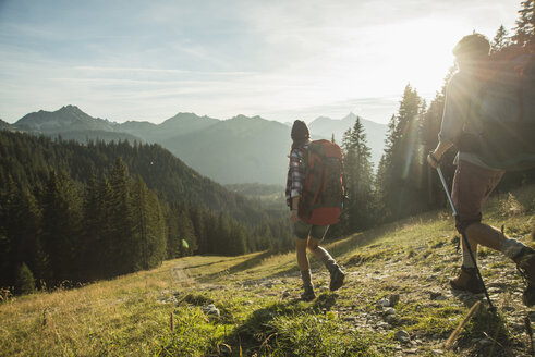 Austria, Tyrol, Tannheimer Tal, young couple hiking in sunlight on alpine meadow - UUF002145