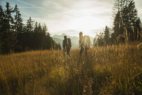 Austria, Tyrol, Tannheimer Tal, young couple hiking in sunlight on alpine meadow - UUF002143