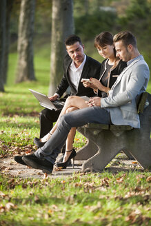 Three business people sitting on a park bench using laptop, smartphone and digital tablet - PAF001013
