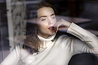 Portrait of pensive young woman looking through window pane of a cafe - GDF000502