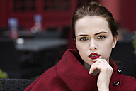 Portrait of young woman with red lips wearing red cape - GD000486