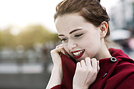 Portrait of daydreaming young woman with red lips wearing red cape - GD000485