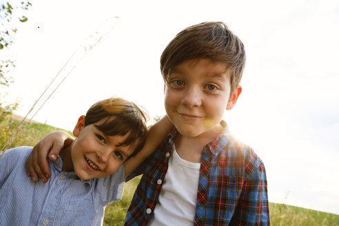Portrait of two smiling little boys at backlight - FKIF000062