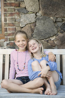 Portrait of two smiling girls sitting on a bench - FKIF000075