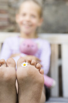 Girl's foot holding daisy - FKIF000039