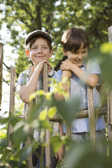 Portrait of two smiling boys standing behind a wooden fence - FKIF000041