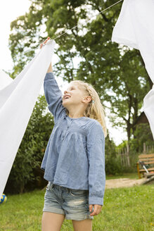 Smiling little girl in the garden with clothesline - FKIF000046