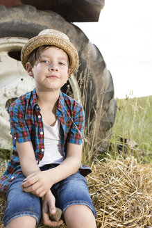 Portrait of smiling little boy sitting on  a straw bale wearing straw hat - FKIF000049