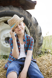 Portrait of smiling little boy sitting on  a straw bale wearing straw hat - FKIF000050