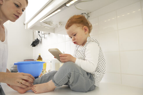 Little girl sitting on kitchen counter with smartphone - FSF000239