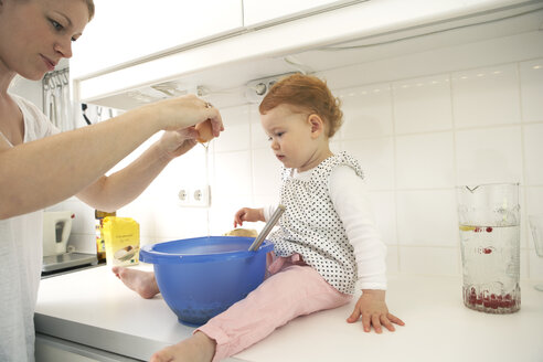 Mother and little daughter baking cake together in their kitchen - FSF000209