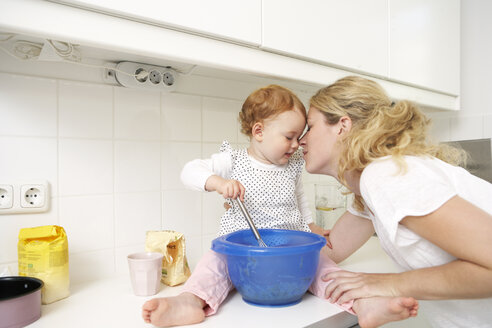 Mother and little daughter baking cake together in their kitchen - FSF000212