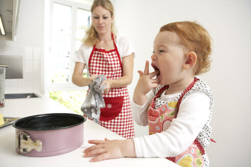 Mother and little daughter baking cake together in their kitchen - FSF000219