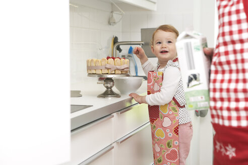 Mother and little daughter baking cake together in their kitchen - FSF000223