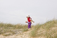 Happy little girl running on a beach dune - JFEF000475
