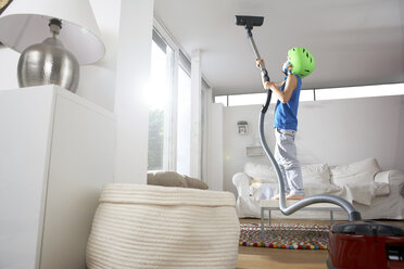 Boy in living room hoovering the ceiling - FSF000271