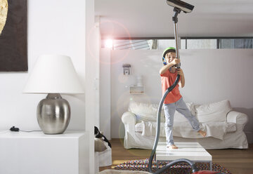 Boy in living room hoovering the ceiling - FSF000273
