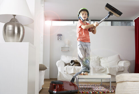 Boy in living room tangled in vacuum cleaner - FSF000276