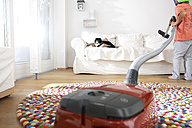 Boy in living room hoovering the sofa with cat - FSF000277