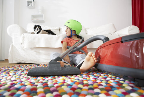 Boy in living room with cat and vacuum cleaner - FSF000281
