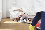 Boy in living room hoovering under carpet - FSF000254