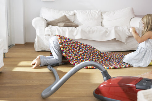 Boy in living room hoovering under carpet - FSF000255