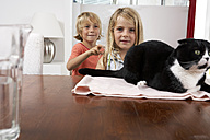 Brother and sister with cat on dining table - FSF000282