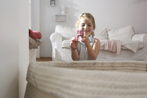 Girl at home playing with pig figurine - FSF000258