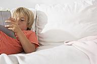 Boy lying on couch using digital tablet - FSF000259