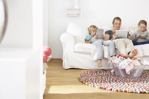 Mother, daughter and son on couch using digital tablet and cell phone with laundry basket on floor - FSF000263